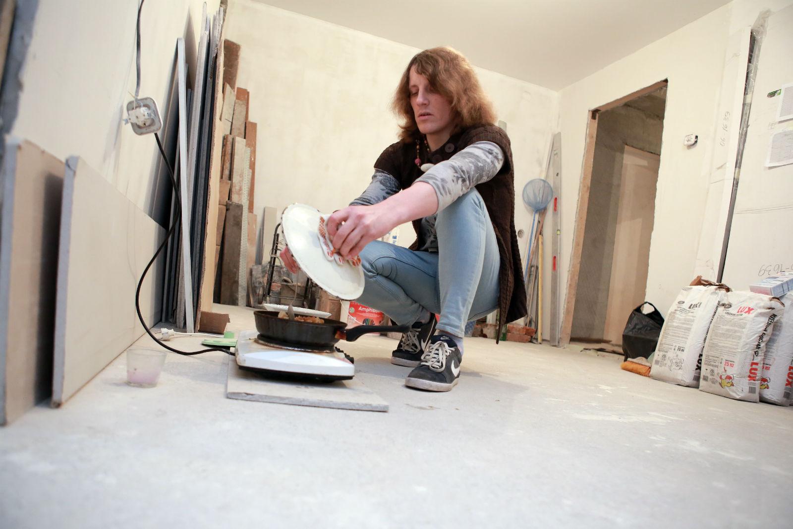 Alina se prépare à manger sur des plaques électriques d'appoint. Elle dort sur un vieux matelas à même le sol et lave son linge dans une poubelle.