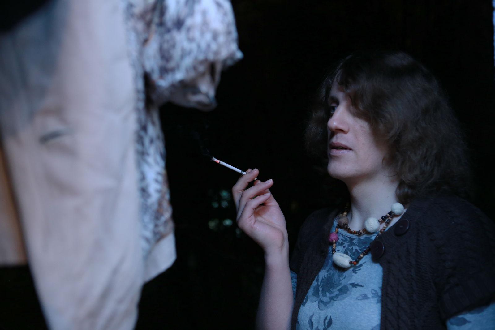 Alina fumant une cigarette sur son balcon.