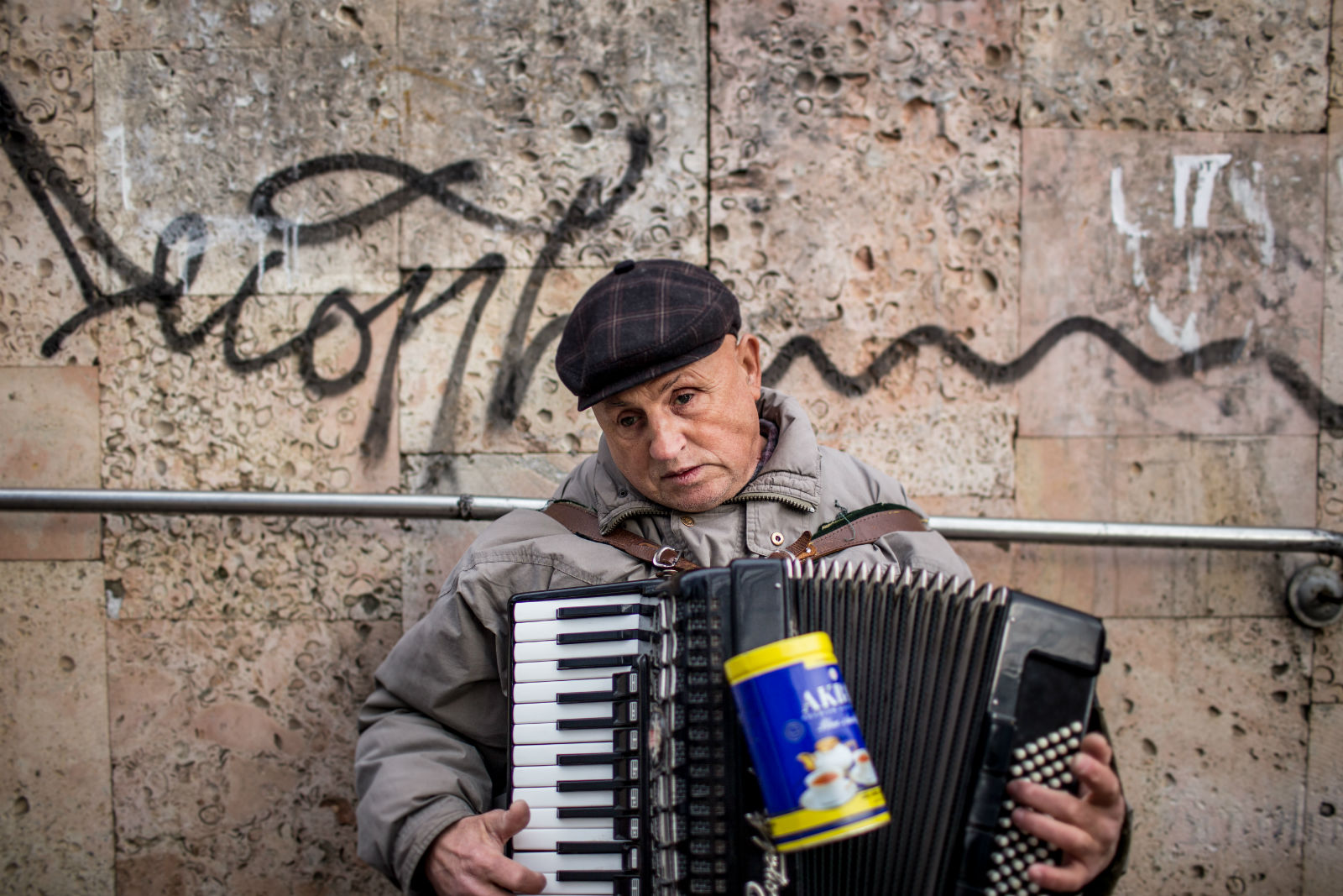 A blind street musician plays the accordion by the entrance of an underground crossing in centre of Chișinău.